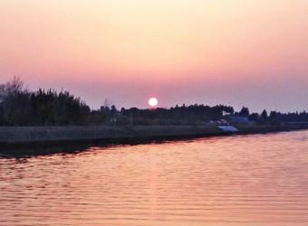 南白亀川の河口付近に沈む夕陽(その2)。流れる時間に身をまかせ、ゆっくりと眺めていたい。