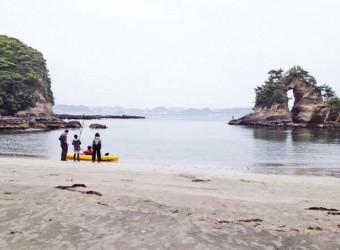 勝浦の尾名浦海岸。これからカヌーをするのだろうか。右側には海蝕によってできた奇岩「めがね岩」。